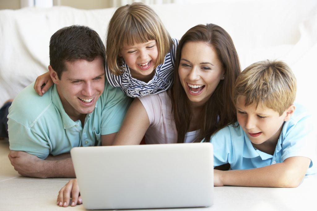 Young parents, with children, on laptop computer